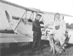 Cal, Canada's first parachuting dog, with his owner, Harold Brooker, and the airplane pilot.